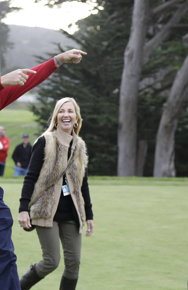Kenny Perry, left, with his wife Sandy, center, points at Fred Couples, right, as they walk to the 18th green to accept their trophies after the final round of the Charles Schwab Cup Championship Champions Tour golf tournament Sunday, Nov. 3, 2013, in San Francisco. Couples won the tournament