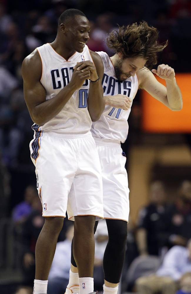 Charlotte Bobcats' Bismack Biyombo (0) and Josh McRoberts (11) celebrate the Bobcats' 124-94 win over the Portland Trail Blazers during the second half of an NBA basketball game in Charlotte, N.C., Saturday, March 22, 2014