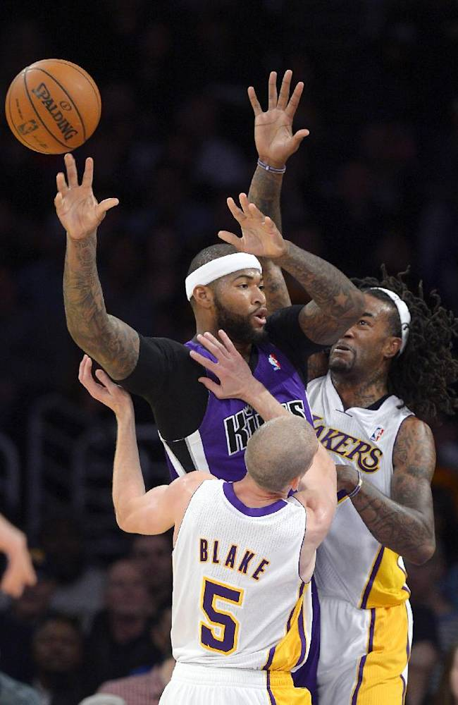 Sacramento Kings center DeMarcus Cousins, center, passes the ball as Los Angeles Lakers guard Steve Blake, front, and center Jordan Hill defend during the first half of an NBA basketball game Sunday, Nov. 24, 2013, in Los Angeles