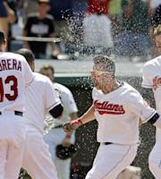 Cleveland Indians' Nick Swisher, second from right, is doused with water as he reaches home plate after a 10th inning grand slam to beat the Los Angeles Angels 5-3 in a baseball game Thursday, June 19, 2014, in Cleveland. (AP Photo/Mark Duncan)