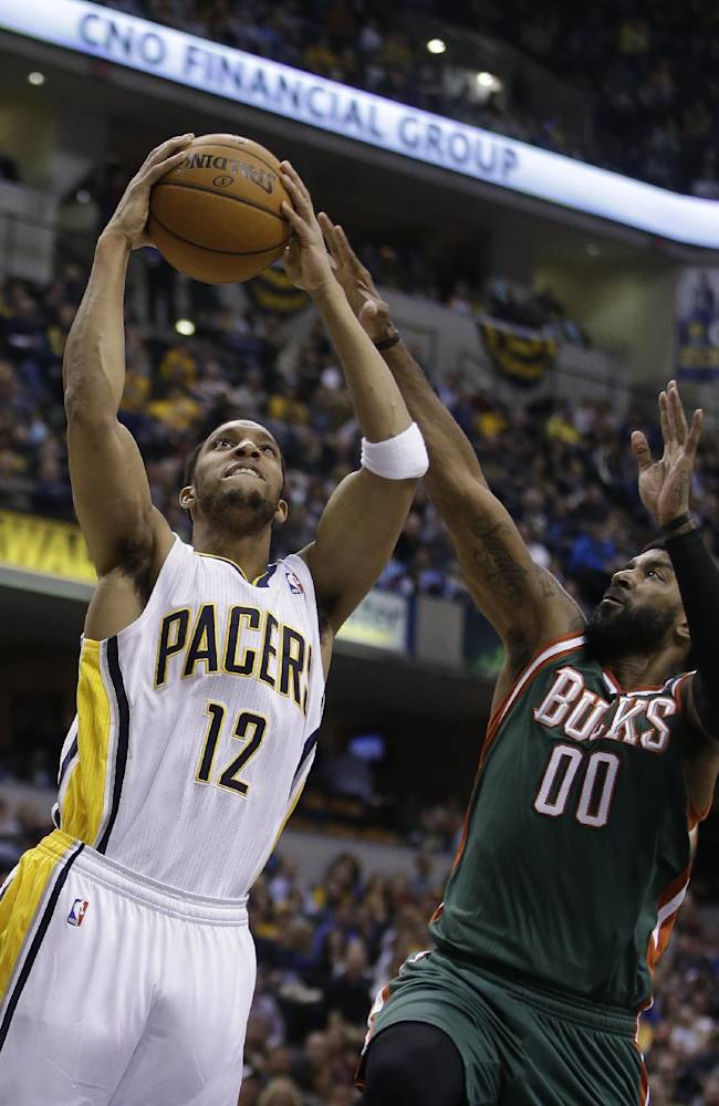 Indiana Pacers' Evan Turner (12) is fouled by Milwaukee Bucks' O.J. Mayo while going up to shoot during the second half of an NBA basketball game on Thursday, Feb. 27, 2014, in Indianapolis. Indiana defeated Milwaukee 101-96