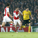 Dortmund's Henrikh Mkhitaryan, right, battles for the ball with Arsenal's Aaron Ramsey and Mathieu Flamini, left, during the Champions League group D soccer match between Arsenal and Borussia Dortmund at the Emirates stadium in London, Wednesday, Nov. 26,
