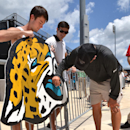 Dalton Dee, left, a student from Fleming Island, holds a large jaguar head he painted for Jacksonville Jaguars head coach Gus Bradley to sign after the NFL team's football training camp, on Friday, July 25, 2014, in Jacksonville, Fla The Associated Press