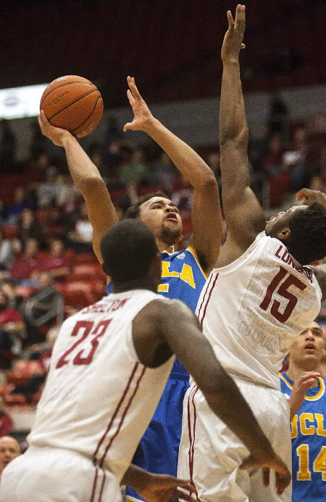 UCLA guard Kyle Anderson, center, shoots over Washington State forward Junior Longrus (15) as forward D.J. Shelton (23) watches during the first half of an NCAA college basketball game Saturday, March 8, 2014, at Beasley Coliseum in Pullman, Wash