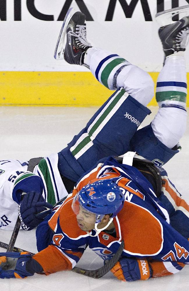 Vancouver Canucks' Kellan Lain is tripped up by Edmonton Oilers' Darnell Nurse, 74, during second period pre-season NHL hockey action in Edmonton, Alta., on Saturday Sept. 21, 2013