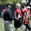 San Francisco 49ers head coach Jim Harbaugh, left, shakes hands with tight end Vernon Davis (85) during NFL football practice in Santa Clara, Calif., Wednesday, May 22, 2013. (AP Photo/Jeff Chiu)