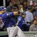 Texas Rangers' Mike Napoli swings on a two-run home run against the Boston Red Sox during the fourth inning of a baseball game at Fenway Park in Boston, Wednesday, April 18, 2012. (AP Photo/Elise Amendola)