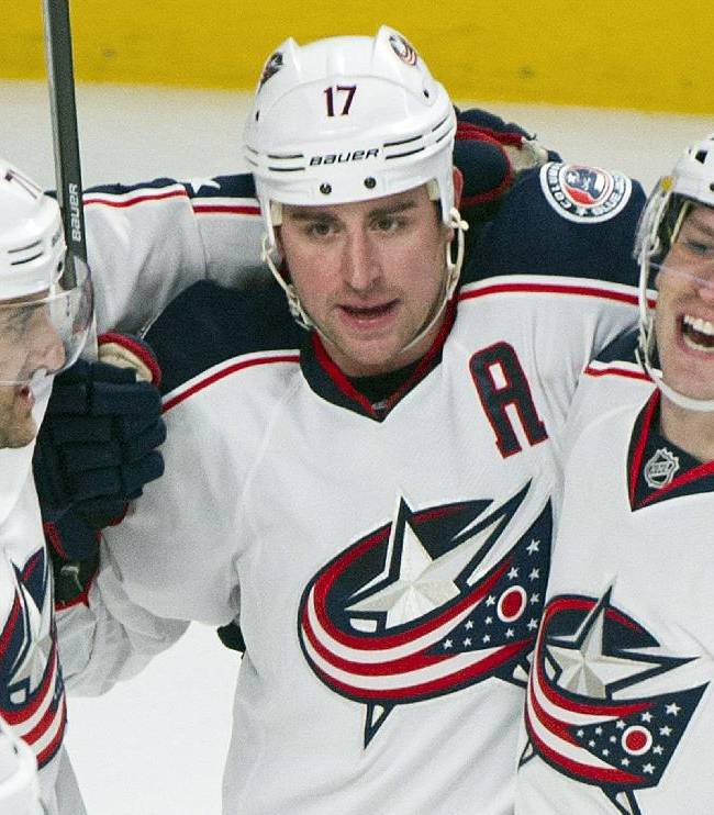 Columbus Blue Jackets' Brandon Dubinsky, center, celebrates with teammates Nick Foligno, left, and Blake Comeau after scoring against the Montreal Canadiens during the second period of an NHL hockey game in Montreal, Thursday, March 20, 2014