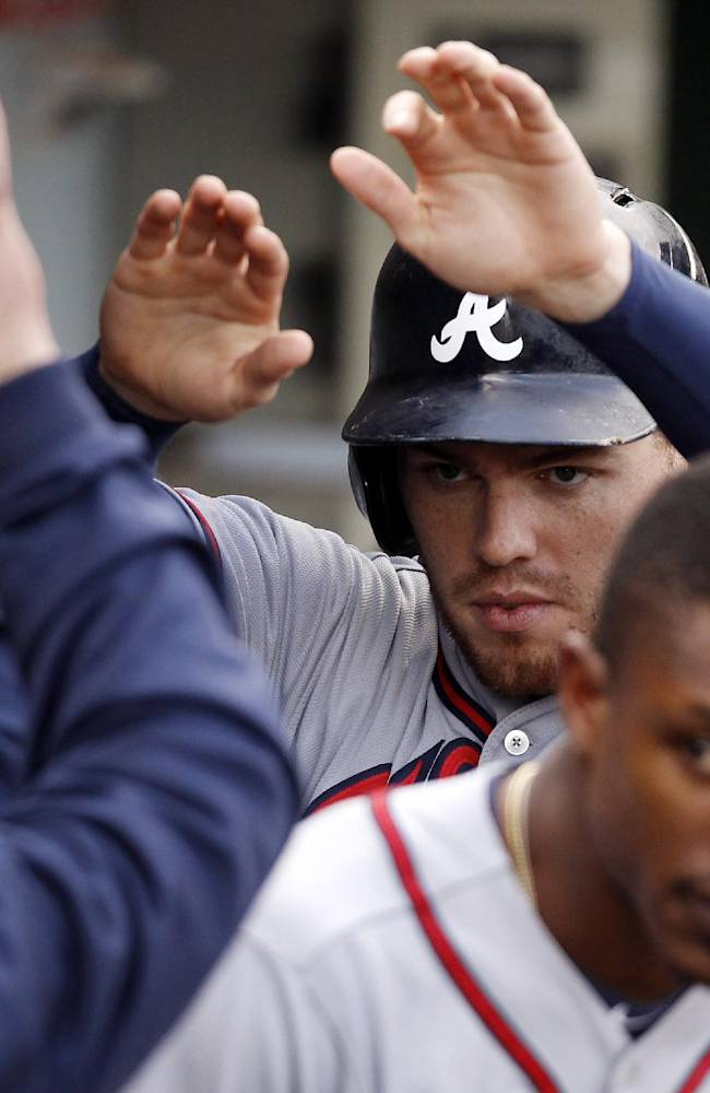 Atlanta Braves' Freddie Freeman celebrates after scoring against the Chicago Cubs during the fourth inning of a baseball game on Saturday, Sept. 21, 2013, in Chicago