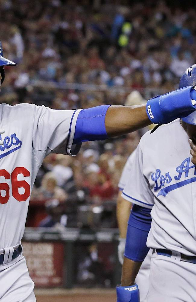 Los Angeles Dodgers' Yasiel Puig (66) points to teammate Adrian Gonzalez, who singled in Puig and Hanley Ramirez, right, during the third inning of a baseball game against the Arizona Diamondbacks on Friday, April 11, 2014, in Phoenix. The Dodgers won 6-0