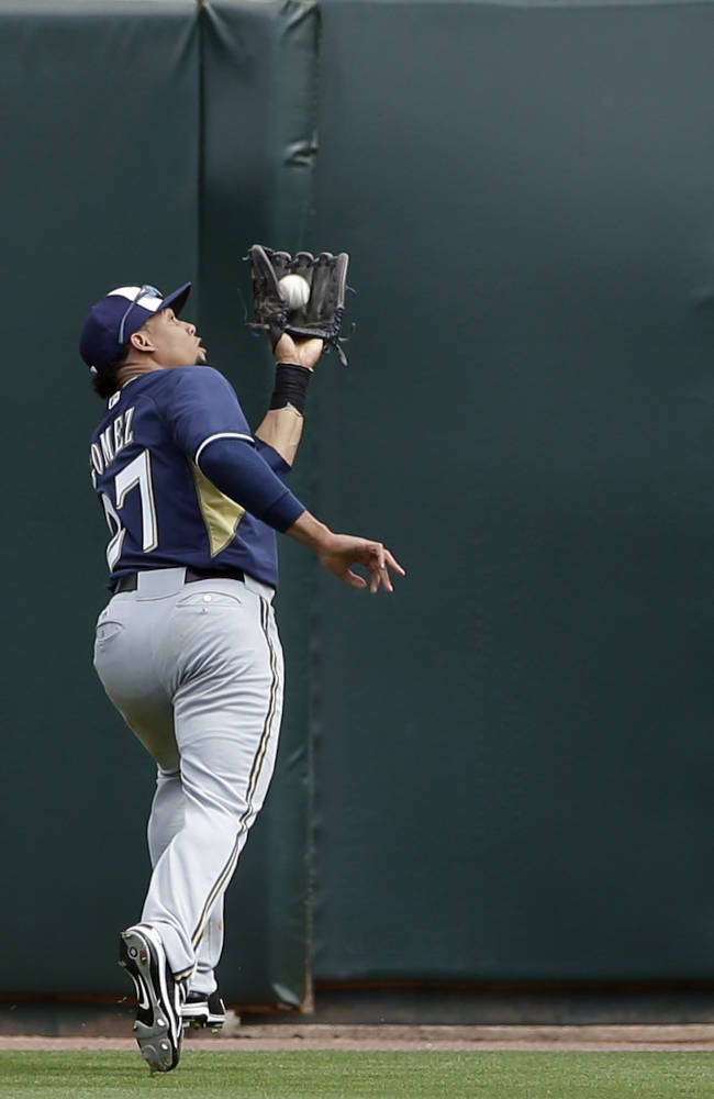 Milwaukee Brewers center fielder Carlos Gomez makes the catch hit by Oakland Athletics' Sam Fuld during the second inning of a spring training baseball game, Thursday, Feb. 27, 2014, in Scottsdale, Ariz