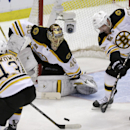 Boston Bruins defenseman Johnny Boychuk (55) helps keep the puck away from Boston Bruins goalie Tuukka Rask of Finland during the third period of Game 3 of a first-round NHL hockey playoff series against the Detroit Red Wings in Detroit, Tuesday, April 22