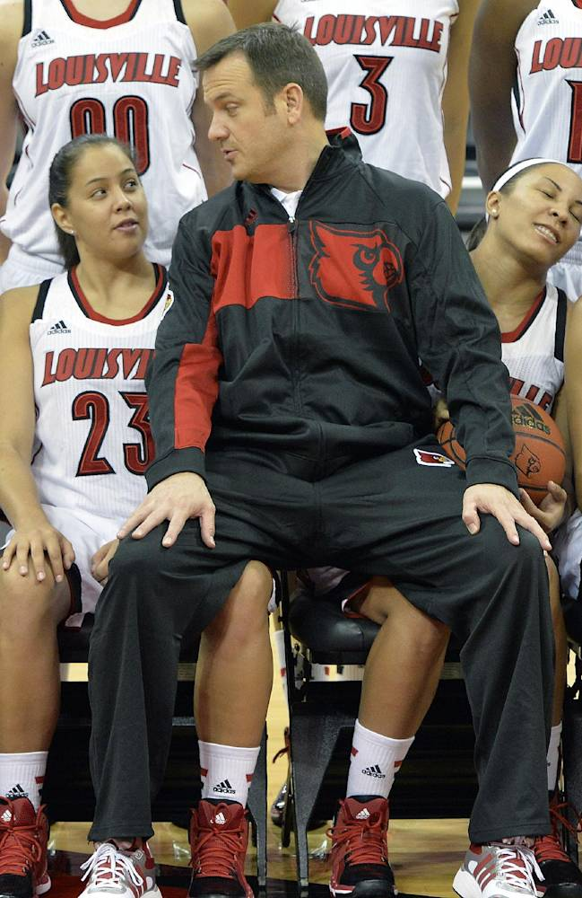 Louisville women's head coach Jeff Walz, center, sits on the laps of Shoni Schimmel, left and Tia Gibbs before the team's photo at NCAA college basketball media day Friday, Nov. 1, 2013, in Louisville, Ky