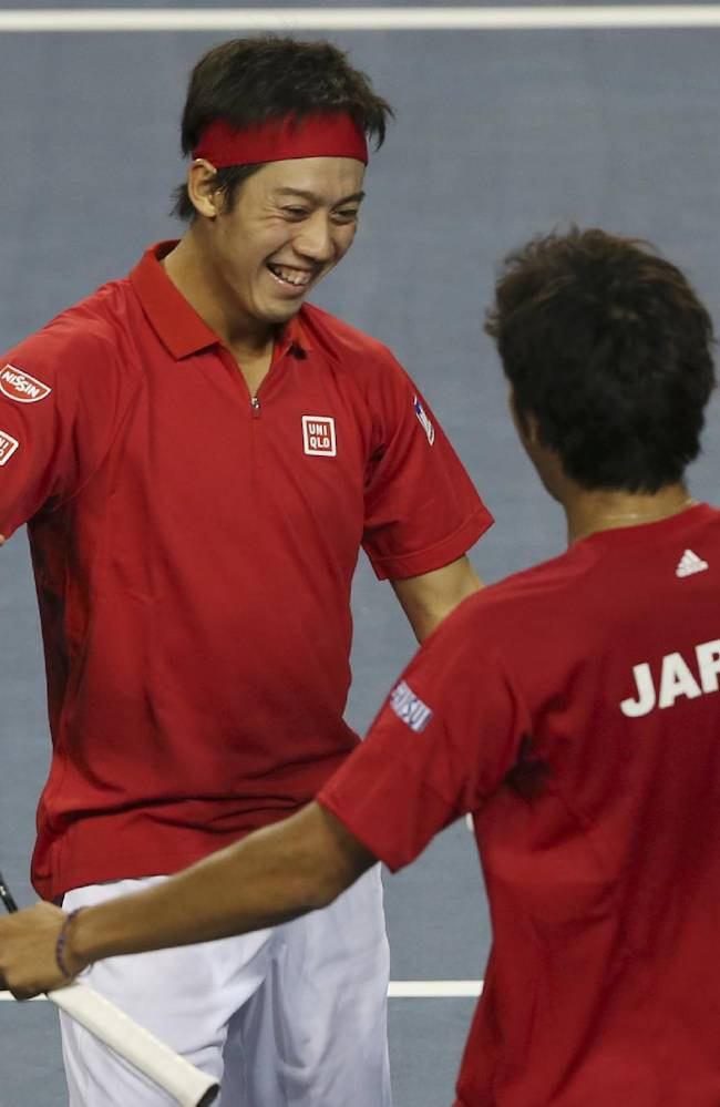 Kei Nishikori of Japan, left, celebrates with his compatriot Yasutaka Uchiyama following their win over Canada during their 1st round of Davis Cup World Group doubles tennis match in Tokyo, Saturday, Feb. 1, 2014. Japan won the match 6-3, 7-6 (3), 4-6, 6-4