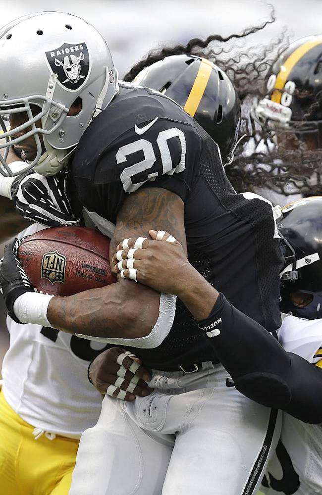 Oakland Raiders running back Darren McFadden (20) runs for a 7-yard touchdown past Pittsburgh Steelers strong safety Troy Polamalu, rear, free safety Ryan Clark, bottom right, and defensive tackle Vance Walker (98) during the first quarter of an NFL football game in Oakland, Calif., Sunday, Oct. 27, 2013