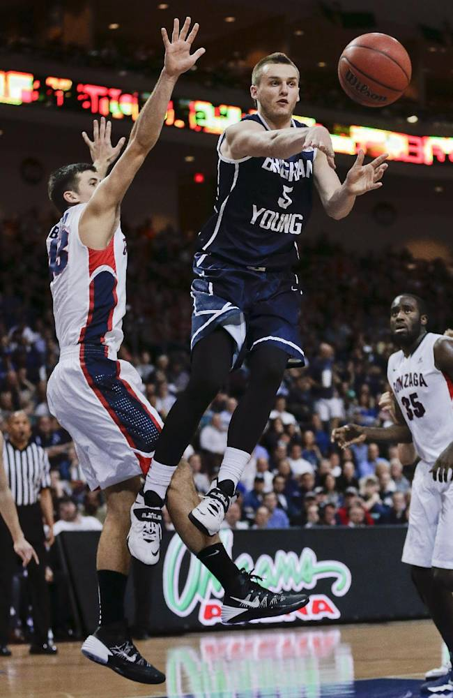 BYU's Kyle Collinsworth (5) passes off the ball against Gonzaga's Drew Barham, left, during the second half of an NCAA college basketball game for the West Coast Conference men's tournament title, March 11, 2014, in Las Vegas. Gonzaga won 75-64