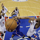 Los Angeles Clippers' Jared Dudley, center, goes up for a shot against Philadelphia 76ers' Tony Wroten, left, and Thaddeus Young during the first half of an NBA basketball game, Monday, Dec. 9, 2013, in Philadelphia The Associated Press