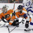 Philadelphia Flyers' Steve Mason, left, blocks a shot by Tampa Bay Lightning's Victor Hedman, right, of Sweden, as Nick Schultz looks on during the first period of an NHL hockey game, Tuesday, Dec. 16, 2014, in Philadelphia The Associated Press