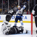Winnipeg Jets center Bryan Little, upper right, celebrates a goal by right wing Blake Wheeler as Los Angeles Kings center Trevor Lewis defends and goalie Jonathan Quick lays on the ice during the first period of an NHL hockey game, Saturday, Jan. 10, 201