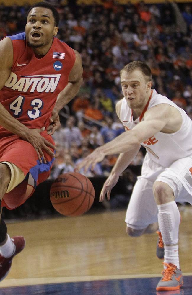 Syracuse's Trevor Cooney (10) knocks the ball away from Dayton's Vee Sanford (43) during the first half of a third-round game in the NCAA men's college basketball tournament in Buffalo, N.Y., Saturday, March 22, 2014