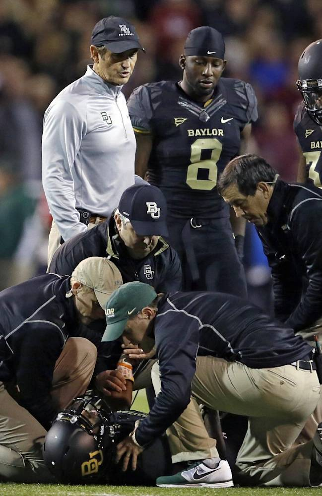 Baylor head coach Art Briles, top left, Glasco Martin (8) and Shock Linwood (32) watch as staff members attend to an injured Lache Seastrunk, bottom, in the first half of an NCAA college football game against Oklahoma, Thursday, Nov. 7, 2013, in Waco, Texas
