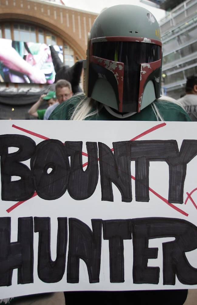 Courtney Wilson of Frisco wears a Star Wars character helmet as she holds up a sign showing her support of the Dallas Stars before a first-round NHL hockey Stanley Cup playoff series game against the Anaheim Ducks, Monday, April 21, 2014, in Dallas