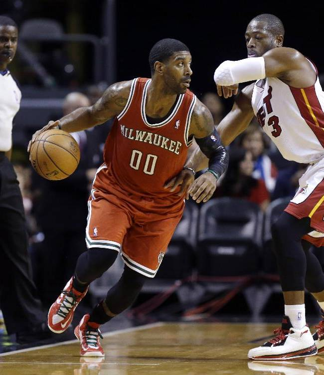Milwaukee Bucks' O.J. Mayo (00) drives to the basket as Miami Heat's Dwyane Wade defends during the first half of an NBA basketball game Tuesday, Nov. 12, 2013, in Miami