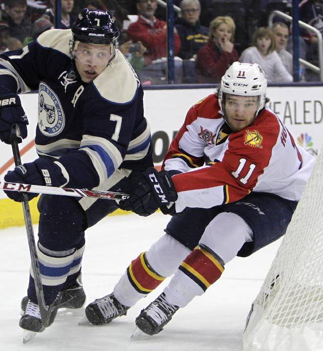 Columbus Blue Jackets' Jack Johnson, left, clears the puck as Florida Panthers' Jonathan Huberdeau defends during the first period of an NHL hockey game on Saturday, Feb. 1, 2014, in Columbus, Ohio