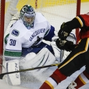Vancouver Canucks goalie Ryan Miller, left, blocks the net on a shot from Calgary Flames' Brian McGrattan during third period NHL hockey action in Calgary, Alberta, Wednesday, Oct. 8, 2014 The Associated Press