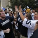Penn State University quarterback Matt McGloin, left, and his teammates are greeted by a pep rally of supporters on the way to a morning workout outside the Lasch Football building on the Penn State main campus in State College, Pa., Tuesday, July 31, 2012. (AP Photo/Gene J. Puskar)