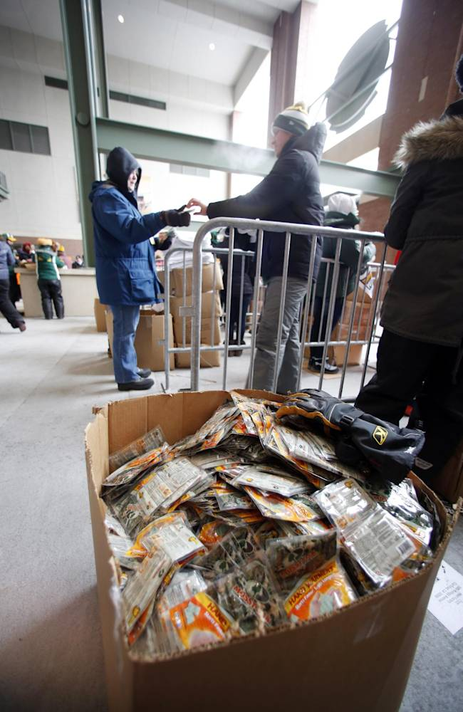 Fans receive free hand warmers as they arrive at Lambeau Field for an NFL wild-card playoff football game between the Green Bay Packers and the San Francisco 49ers, Sunday, Jan. 5, 2014, in Green Bay, Wis