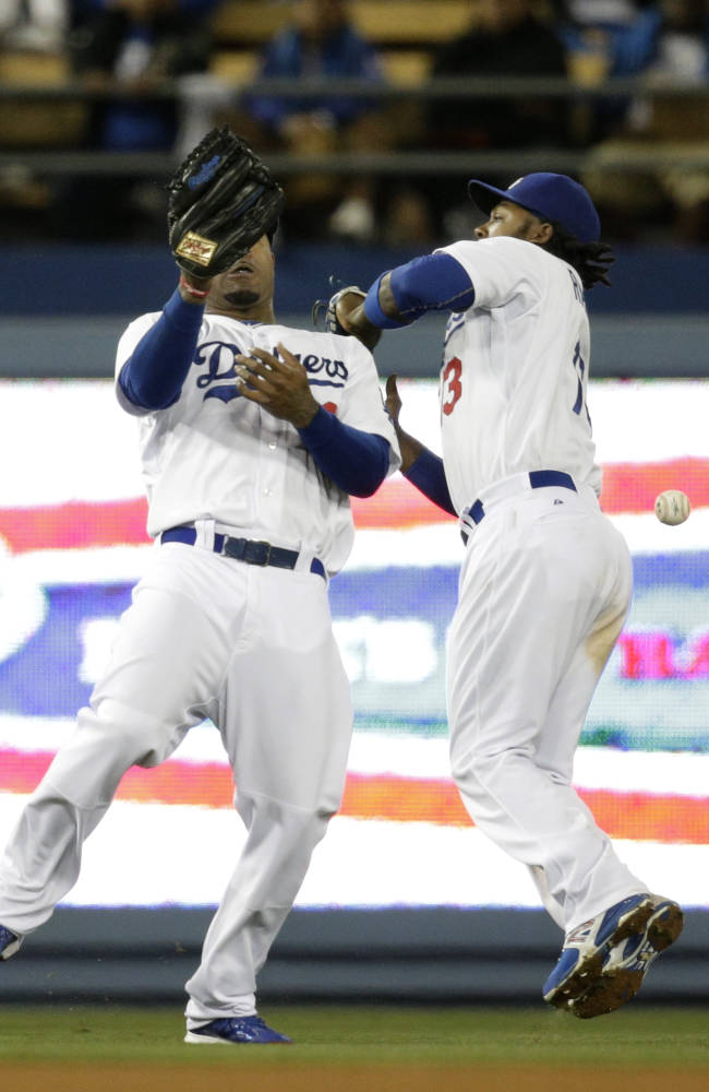 Los Angeles Dodgers' Carl Crawford, left, and Hanley Ramirez misses the ball hit by Philadelphia Phillies' Carlos Ruiz during the 10th inning of a baseball game on Tuesday, April 22, 2014, in Los Angeles