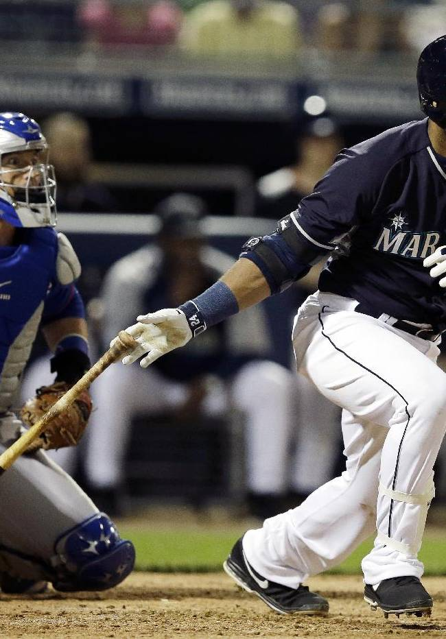Seattle Mariners' Robinson Cano, right, hits an RBI-double during the first inning of a spring exhibition baseball game against the Chicago Cubs, Wednesday, March 12, 2014, in Peoria, Ariz