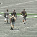 In this photo taken on Aug. 15, 2014, Eastern Michigan players walk across the field before NCAA college football practice at Rynearson Stadium in Ypsilanti, Mich.. The school has replaced the stadium's green artificial turf with gray FieldTurf