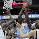 Denver Nuggets forward Kenneth Faried (35) attempts a shot as Dallas Mavericks' Samuel Dalembert (1) and Dirk Nowitzki (41) defend during the first half of an NBA basketball game Monday, Nov. 25, 2013, in Dallas The Associated Press