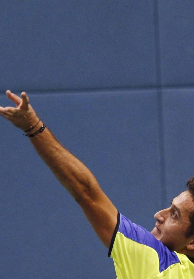 Nicolas Almagro of Spain tosses the ball to serve against Go Soeda of Japan at the single match of the Shanghai Masters tennis tournament at Qizhong Forest Sports City Tennis Center in Shanghai, China, Tuesday, Oct. 8, 2013. Almagro won 7-6, 6-2. (AP Photo)
