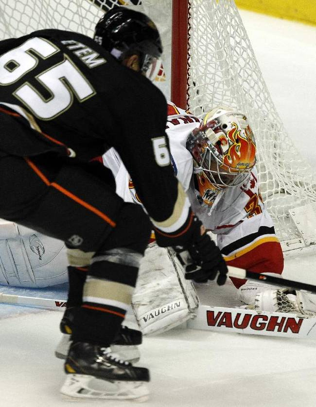 Calgary Flames goalie Joey MacDonald (35) rejects a shot by Anaheim Ducks right wing Emerson Etem (65) during the third period of an NHL hockey game, Wednesday, Oct. 16, 2013, in Anaheim, Calif. Ducks won the game 3-2