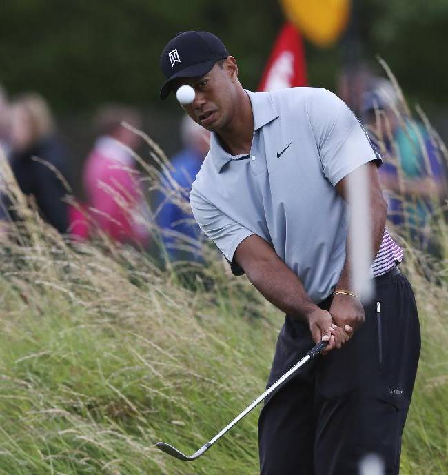 10ThingstoSeeSports - Tiger Woods watches his shot on the practice chipping green ahead of the British Open Golf championship at the Royal Liverpool golf club, Hoylake, England, Wednesday July 16, 2014