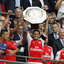 Arsenal's Mikel Arteta raises the trophy after their win against Manchester City at the end of their English Community Shield soccer match at Wembley Stadium in London, Sunday, Aug. 10, 2014