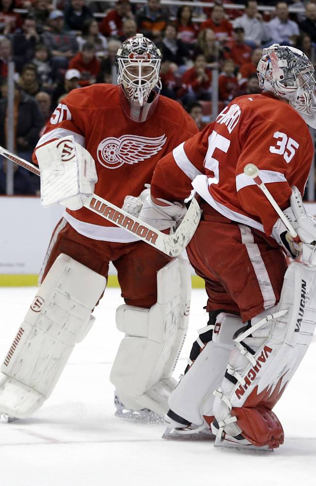 Detroit Red Wings goalie Jonas Gustavsson, left, pats goalie Jimmy Howard after replacing him during the first period of an NHL hockey game against the Ottawa Senators in Detroit, Wednesday, Oct. 23, 2013
