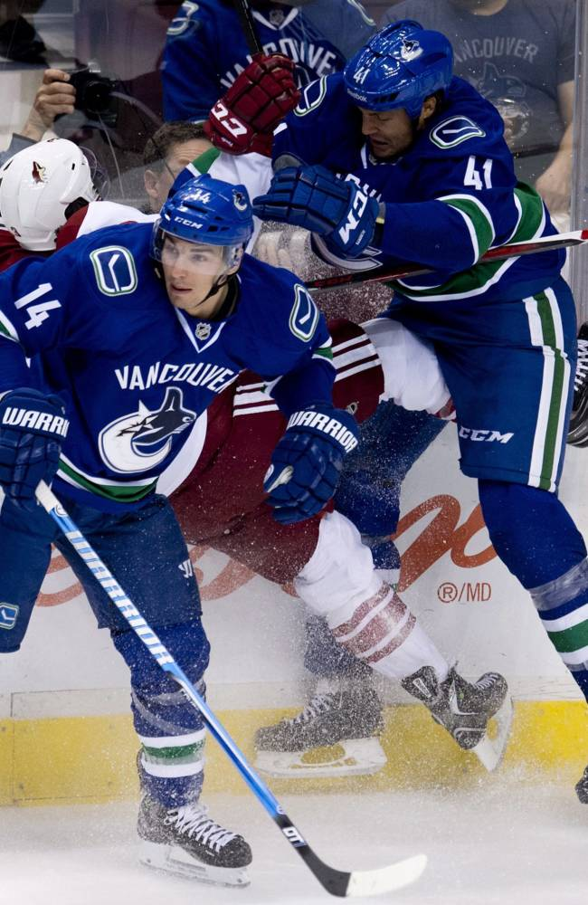 Vancouver Canucks defenseman Andrew Alberts (41) puts Phoenix Coyotes defenseman Keith Yandle (3) into the boards as Vancouver Canucks center Alex Burrows (14) looks on during the first period of NHL pre-season hockey action at Rogers Arena in Vancouver, British Columbia, Monday, Sept. 23, 2013