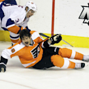 Philadelphia Flyers' Steve Downie (9) loses his helmet after being checked by New York Islanders' Travis Hamonic (3) in the third period of an NHL hockey game, Saturday, Nov. 23, 2013, in Philadelphia. Flyers won 5-2 The Associated Press