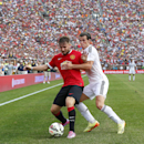 Manchester United defender Alexander Buttner, left, protects the ball from Real Madrid midfielder Gareth Bale during a Guinness International Champions Cup soccer match at Michigan Stadium in Ann Arbor, Mich., Saturday, Aug. 2, 2014. Manchester United won