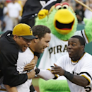 Pittsburgh Pirates' Russell Martin, center, is greeted by teammates Jeanmar Gomez, left, and Josh Harrison after Martin drove in Gaby Sanchez with a pinch-hit in the 14th inning of the baseball game against the Milwaukee Brewers on Sunday, June 30, 2013, in Pittsburgh. The Pirate mascot