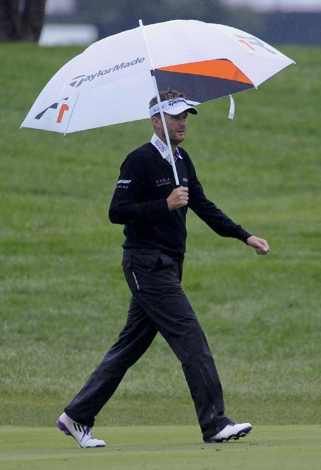 David Lynn walks the first fairway under an umbrella as rain falls during the final round of the BMW Championship golf tournament at Conway Farms Golf Club in Lake Forest, Ill., Sunday Sept. 15, 2013
