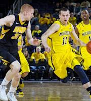 Iowa forward Aaron White (30) defends Michigan guard Nik Stauskas (11) in the first half of an NCAA college basketball game in Ann Arbor, Mich., Wednesday, Jan. 22, 2014. (AP Photo/Tony Ding)