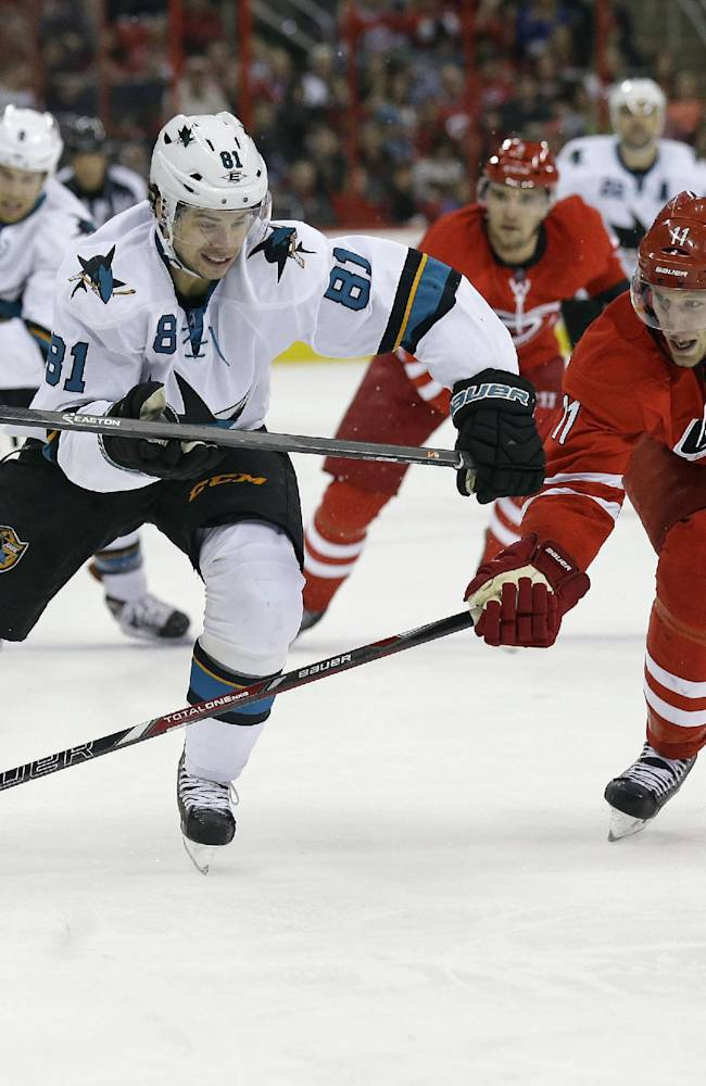 San Jose Sharks' Tyler Kennedy (81) and Carolina Hurricanes' Jordan Staal (11) chase the puck during the first period of an NHL hockey game in Raleigh, N.C., Friday, Dec. 6, 2013