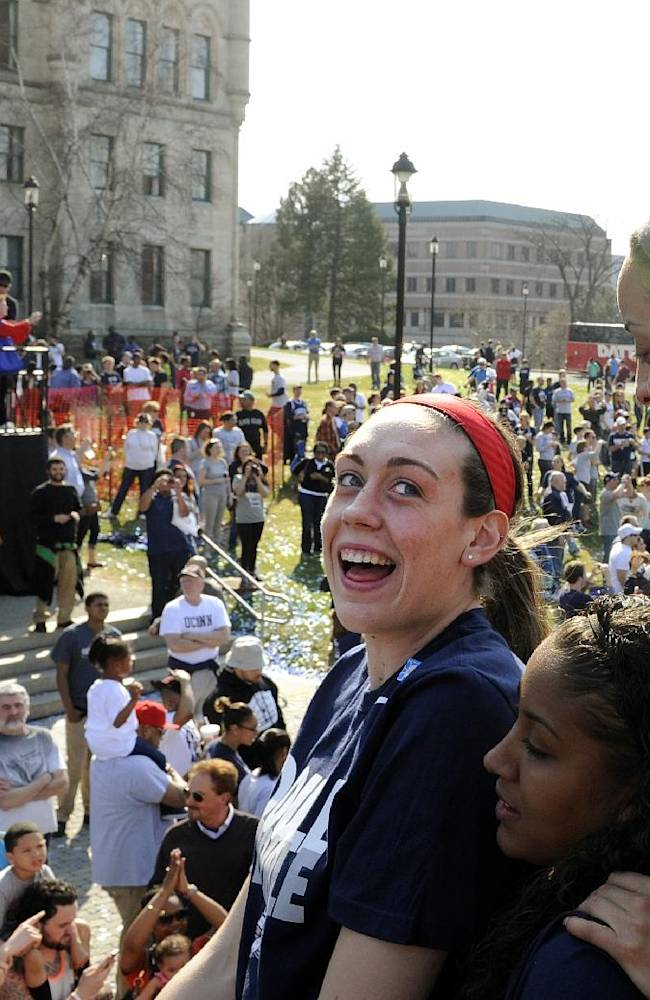 Connecticut's Breanna Stewart, center, looks back at Bria Hartley, top right, and Kaleena Mosqueda-Lewis, bottom, during a parade celebrating their team's NCAA women's college basketball championship, in Hartford, Conn., on Sunday, April 13, 2014