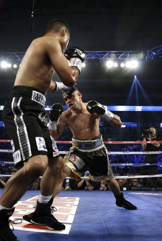 Miguel Angel Garcia, front, fights off an advance from Juan Manuel Lopez, rear, of Puerto Rico in the third round of their World Boxing Organization featherweight title fight boxing match Saturday, June 15, 2013, in Dallas. Garcia won the fight in the fourth round by technical knock out