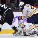 Los Angeles Kings right wing Dustin Brown, left, tries to get a shot in on Buffalo Sabres goalie Jhonas Enroth, center, of Sweden, as left wing Matt Moulson defends during the third period of an NHL hockey game, Thursday, Oct. 23, 2014, in Los Angeles. T